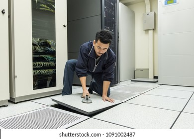 Soft focus Technician Lifting Floor Tile Using Vacuum Suction Cups. Open Lifting Floor in Datac or Server room.