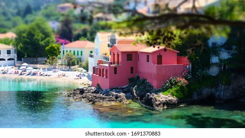 Soft focus and tilt shift  blur. Colorful Asos village at Kefalonia island. Greece. People relaxing, sunbathing on sand and swimming in turquoise water of Ionian Sea