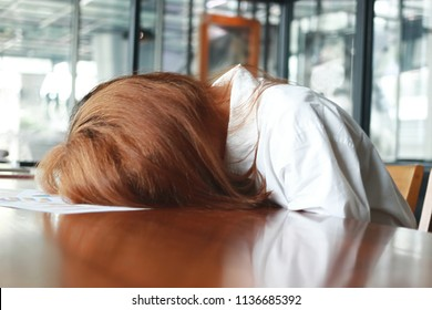 Soft focus of tired stressed young business woman bend down head on the desk in office.