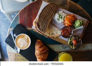 Soft focus top view of breakfast plate, rye wholewheat bread toast, avocado spread, salmon, latte coffee with milk and crispy fresh croissant on wooden artisan cutting board