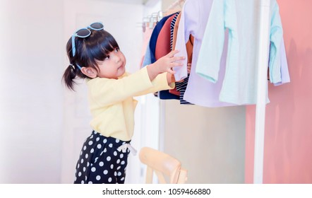 Soft Focus of a Two Years Old Child Choosing her own Dresses from Kids Cloth Rack