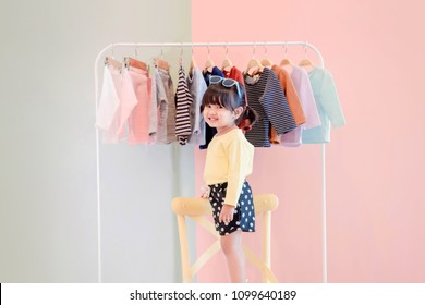Soft Focus of a Two Years Old Child Standing in front of Cloth Rack for Choosing own Dresses, Happy Kids