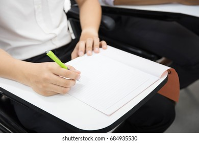soft focus university or high school student holding pencil.sitting on row chair writing final exam in examination room or study in classroom.student in uniform.education concept