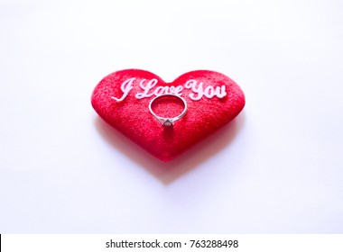 soft focus valentine day concept, diamond ring placed inside a red heart on white background