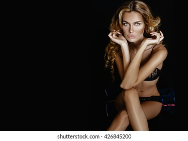 Soft focus. Very beautiful woman model with long blonde curly hair and makeup. Posing on a black background in black lace underwear and a black jacket.