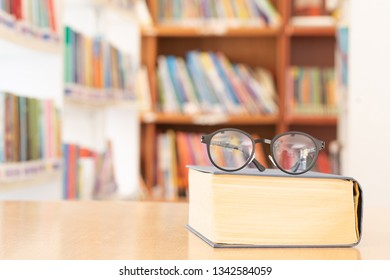 soft focus vintage glasses on books stack on wooden desk in university or public library room or book store,abstract book blur background.concept for education,background.