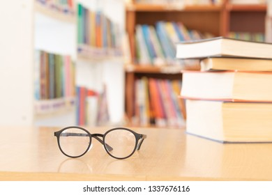 soft focus vintage glasses,blur books stack on wooden desk in university or public library room or book store,abstract book blur background.concept for education,background.