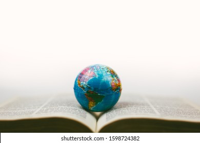 soft focus vintage globe with open Bible and magnifying glass, a missions concept.