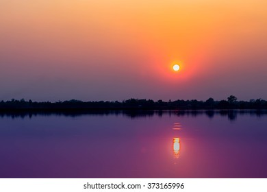 Soft of Focus and Warm Tone Filter : Lonely Sunset Above the Dam with a sunlight shadow effect on water