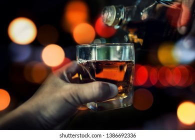 Soft focus of whisky pouring into a glass on light bokeh background.