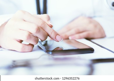 Soft focus of woman doctor touching screen on modern smart phone during the consultation in the workplace hospital.