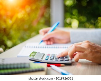 Soft focus woman hand working with calculator and holding blue pen, and note book on working table with nature green leaves background.