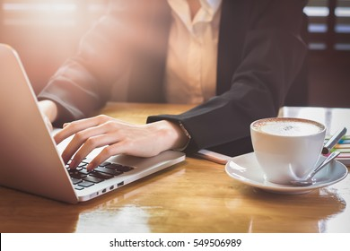 soft focus of woman hand working with phone and laptop on wooden desk in office in morning light. vintage effect