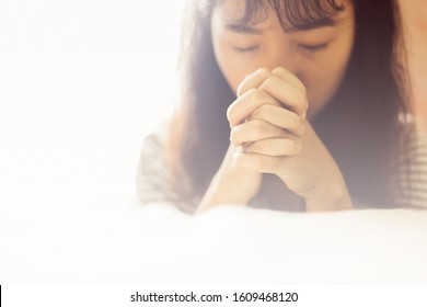 Soft focus Woman are praying and thanks to the Lord, girl prayer,copy space,sunday morning, devotion concept.