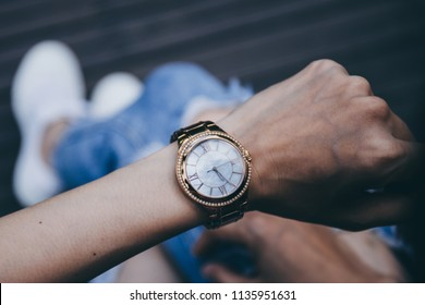 soft focus women in jean,white sneaker sitting outdoor on wooden floor background.looking at watch on hand, watching time. concept for punctuality, appointment