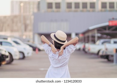 Soft Focus,A girl wearing a hat and a vintage style dress is standing stretch lazily on a parking lot in the morning because of the fatigue of the trip. The girl feels lazy after getting off the car