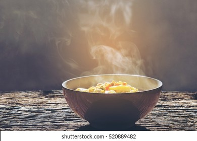 Soft focus.Bowl of hot food with steam on dark background. Vintage tone