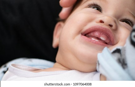 Soft focused baby facial expression, infant is very happy, has. big smile shows his teething gum
