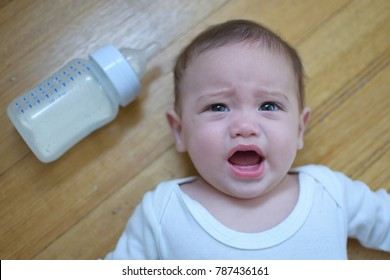 Soft focused four months old baby crying to deny the milk bottle.