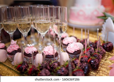 Soft focused shot of festive candy bar with cupcakes, champagne glasses and strawberries in chocolate glaze. Unfocused pink cake on background. Wedding or birthday party concept.