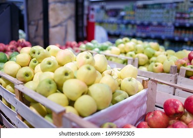 Soft focused shot fruit department in grocery store, supermarket, mall, hypermarket or shopping center. Boxes of multicolored apples. Healthy eating, avitaminosis, diet, organic, vegan food concept.