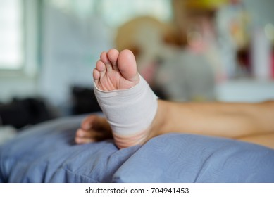 Soft focus.First Aid for ankle woman with elastic bandage and sandal