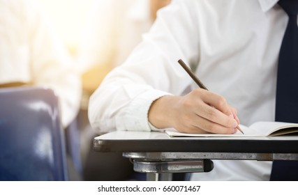 soft focus.front view undergraduate student holding pencil.sitting on lecture chair doing final exam in examination room or study in classroom.university student in uniform.space for text.