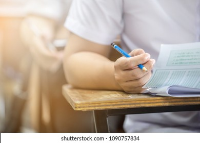 soft focus.hand high school or university student in uniform holding pencil writing on paper answer sheet.sitting on lecture chair taking final exam or study attending in examination room or classroom