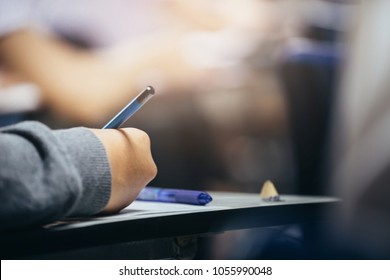 soft focus.high school or university student holding pencil writing on paper answer sheet.sitting on lecture chair taking final exam attending in examination room or classroom.student in casual
