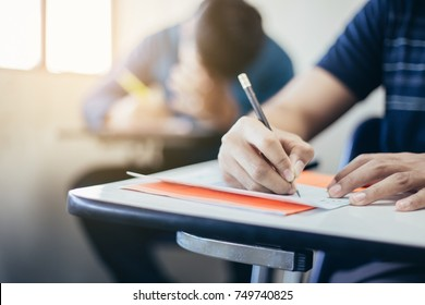 soft focus.high school or university student holding pencil writing on paper answer sheet.sitting on lecture chair taking final exam attending in examination room or classroom.student in casual.