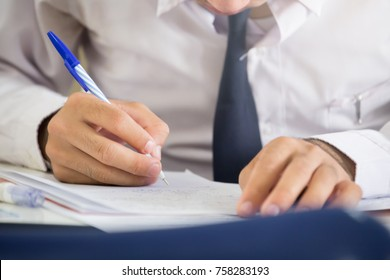 soft focus.high school or university student holding pencil writing on paper answer sheet.sitting on lecture chair taking final exam attending in examination room or classroom.student in uniform