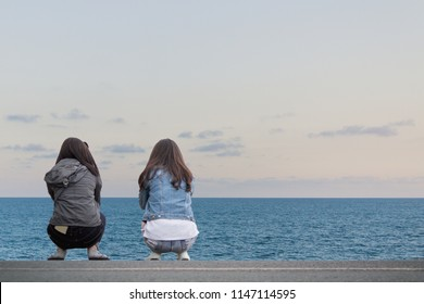 Soft Focus,One girl sitting with her friend on the beach road in the evening to enjoy the beautiful view of the sea in the Gulf of Thailand during the sunset. Love, compassion and friendship