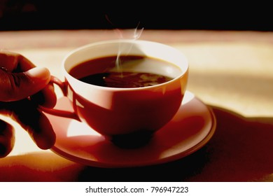 Soft focus,one hand pick up hot black coffee with steam in pink ceramic cup on old wooden table background. Concept for Valentine's Day.