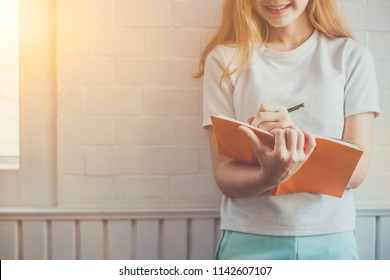 Soft Focus,The girl reads a book by the window in the morning for the light of the sun and warmth in the morning of the summer. Young students are reviewing the lessons and using the ideas to remember