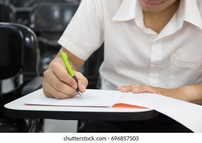 soft focus.university or high school student holding pen.sitting on row chair taking final exam in examination room or study in classroom.student in uniform.education concept