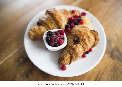 Soft French croissant with blackberries and raspberries. Selective focus at berryies.