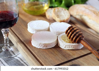 Soft French goat cheese Rocamadour, bread, honey, lettuce and glass of red wine. Focus selective