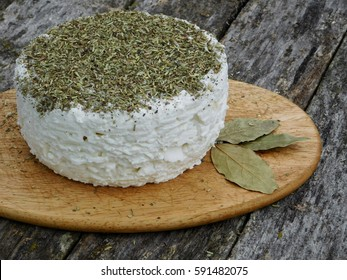 Soft goat cheese with herbs on the old wooden table