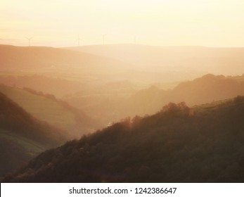 a soft hillside tree covered valley landscape blurred by fog at sunrise glowing a warm orange color with the tops of hills showing though the mist