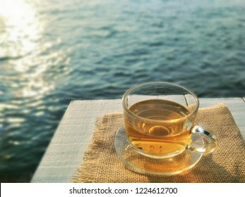 Soft image of glass tea cup set with sackcloth on white wooden tabletop with blurred sunlight and reflection on sea surface background in morning time, enjoy tea time with relaxing on holiday concept