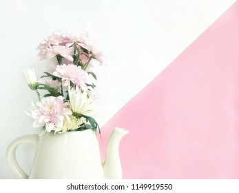 Soft image of pink and white chrysanthemum are blooming in white ceramic teapot with pastel pink and white wall background in flowers decorations and still life concept, close up shot with copy space