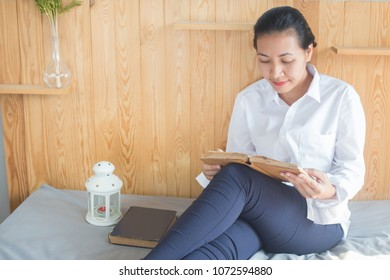 Soft image of young Asain woman reading book on her bed in bedroom