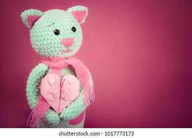 Soft knitted cat and valentine card on pink background. Soft knitted toy. Romantic gift. Copy space