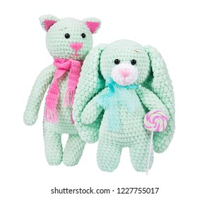 Soft knitted toys and lollipop on white background. Plush crocheted cat with pink scarf. Plush crocheted bunny.