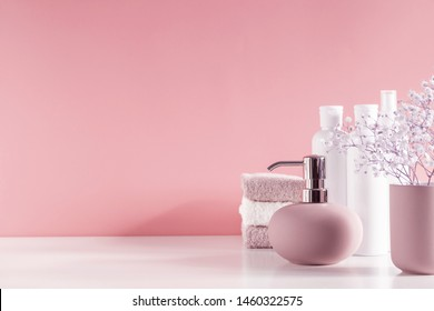 Soft light bathroom decor in pastel pink color, towel, soap dispenser, white flowers, accessories on pastel pink shelf. Elegant decor bathroom interior.