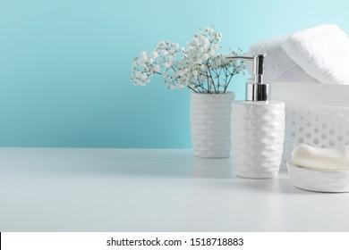 Soft light bathroom decor in white color, towel, soap dispenser, white flowers, accessories on pastel blue shelf. Elegant decor bathroom interior.