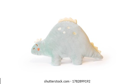 Soft light green plushie doll Stegosaurus dinosaur toy. Object isolated on white background with shadow reflection. The concept of gifts for the holidays. Toy in the shape of an animal. Side wiew