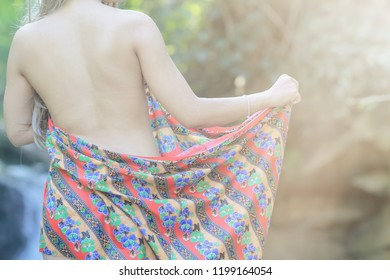 Soft Light and Smooth Focus,Thai girl is happy to play waterfall alone by wearing sarong on the blurred background of the waterfall in the morning. Wear sarong as a way of life of rural people.
