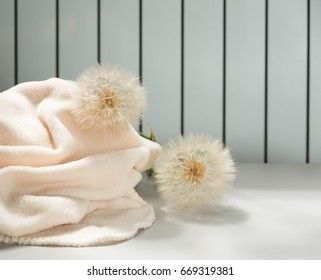 Soft microfiber wrap and big dandelions on light gray background with stripes.