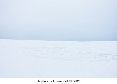 Soft Minimalist Landscape of Snow Field with Snowmobile Tracks and Cloudy Sky